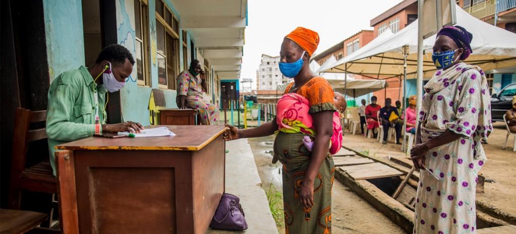 ONU-Mujeres nigerianas toman vales de alimentos como parte de un programa de apoyo a las familias que luchan contra el confinamiento de la COVID-19